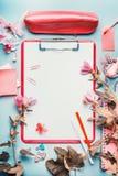 在桃红色红颜色的现代女性家庭办公室桌面与花、辅助部件和空白的剪贴板在蓝色背景,顶视图 免版税库存照片