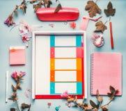 在桃红色红颜色的现代女性家庭办公室桌面与花、辅助部件和计划者钱包在蓝色背景,顶视图 fla 免版税库存照片