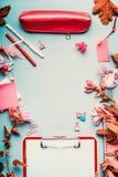 在桃红色红颜色的现代女性家庭办公室桌面与花和辅助部件在蓝色背景,顶视图,框架 平的位置 库存照片