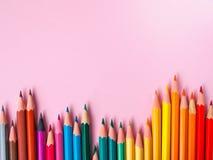 在桃红色纸背景的色的铅笔绘画颜色圈子的 免版税库存图片