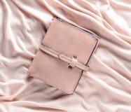 在桃红色织品背景的女性皮革钱包 库存照片