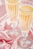 在桃红色缎背景的汽酒 免版税库存图片