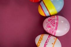 在桃红色背景安排的各种各样的复活节彩蛋 免版税图库摄影