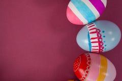 在桃红色背景安排的各种各样的复活节彩蛋 库存照片