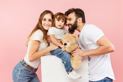 在桃红色背景的一个愉快的家庭 免版税库存照片