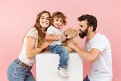 在桃红色背景的一个愉快的家庭 免版税图库摄影