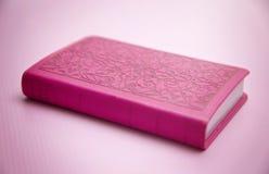 在桃红色背景的一部桃红色圣经 库存照片