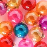 在桃红色背景的五颜六色的透亮玻璃圣诞节中看不中用的物品 创造性的装饰 免版税库存图片
