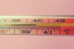在桃红色背景的医疗水银温度表 库存照片