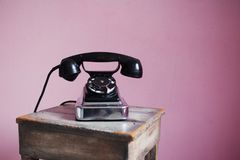 在桃红色背景的古板的黑电话 免版税库存照片