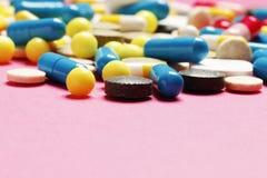在桃红色背景的多彩多姿的维生素 免版税库存图片
