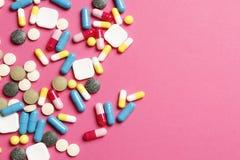 在桃红色背景的多彩多姿的维生素 免版税图库摄影
