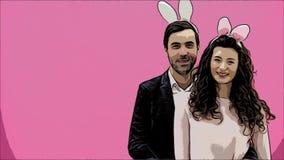 在桃红色背景的年轻创造性的夫妇 使用在头的陈旧耳朵 在此期间,两显示姿态  影视素材
