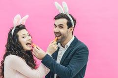 在桃红色背景的年轻愉快的夫妇身分 在兔宝宝的耳朵的头上 在这个人和他的妻子期间 库存照片