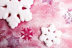 在桃红色背景的桃红色和白色雪花 抽象空白背景圣诞节黑暗的装饰设计模式红色的星形 顶视图 复制空间 装饰雪 图库摄影