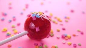 在桃红色背景的桃红色圆的棒棒糖特写镜头 股票录像