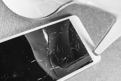 在桃红色背景的残破的手机 免版税库存照片