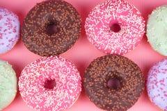 在桃红色背景的甜五颜六色的鲜美油炸圈饼 免版税库存图片