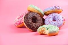 在桃红色背景的甜五颜六色的鲜美油炸圈饼 库存照片