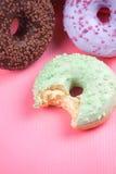 在桃红色背景的甜五颜六色的鲜美油炸圈饼 图库摄影