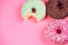在桃红色背景的甜五颜六色的鲜美油炸圈饼 免版税图库摄影