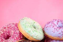 在桃红色背景的甜五颜六色的鲜美油炸圈饼 库存图片