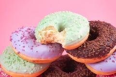在桃红色背景的甜五颜六色的鲜美油炸圈饼 免版税库存照片