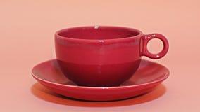 在桃红色背景的红色杯子咖啡 库存照片