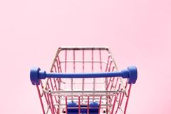 在桃红色背景的跳跃的推车 免版税库存照片