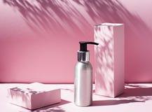 在桃红色背景的金属化妆瓶与苛刻的光 免版税库存照片