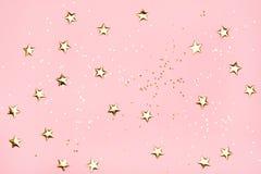 在桃红色背景的金黄星闪烁 库存照片