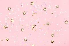 在桃红色背景的金黄星闪烁 库存图片