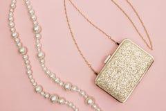 在桃红色背景的金黄钱包和珍珠项链 库存照片