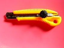 在桃红色背景的黄色切削刀 库存图片