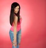 在桃红色背景的年轻女性 免版税库存照片
