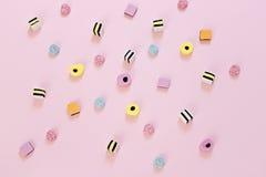 在桃红色背景驱散的色的糖果 免版税库存图片