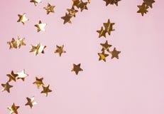 在桃红色背景,顶视图的金黄发光的装饰星 库存图片
