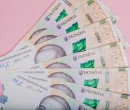 在桃红色背景- hryvnia的现代乌克兰金钱 500张钞票 uah 概念庄园房子货币实际反映 库存照片