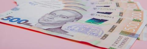 在桃红色背景- hryvnia的现代乌克兰金钱 500张钞票 uah 概念庄园房子货币实际反映 库存图片