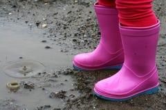 在桃红色胶靴的小女孩在泥水坑的腿和下落  库存照片