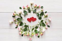 在桃红色自然玫瑰框架的手工制造闪烁心脏在白色土气木头 库存图片