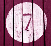 在桃红色被定调子的木墙壁上的第七 图库摄影