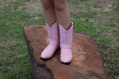 在桃红色起动的女孩的脚 免版税库存照片