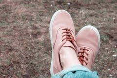 在桃红色运动鞋的女性的脚在草背景,葡萄酒样式 库存图片