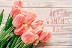 在桃红色郁金香的愉快的妇女` s天文本在白色土气木bac 免版税库存图片