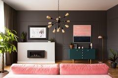 在桃红色长沙发上的灯在与绿色内阁和壁炉的灰色公寓内部 免版税图库摄影