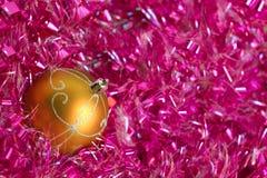 在桃红色闪亮金属片的黄色圣诞节球 免版税库存图片