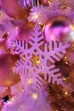 在桃红色颜色光的闪烁雪花和闪烁球形的圣诞节装饰品 免版税库存图片