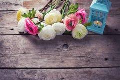 在桃红色颜色的在蓝色灯笼的花和蜡烛在葡萄酒w 库存图片