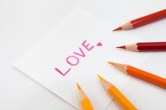 在桃红色颜色的字词爱与在小纸的一点心脏,包围与在温暖的口气的颜色铅笔 免版税库存图片